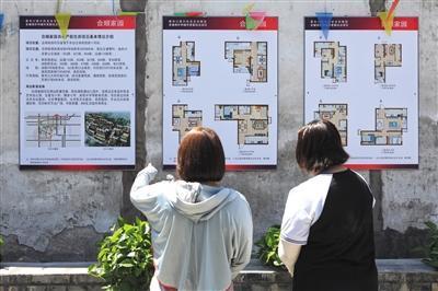 昨日,菜市口附近,市民在申请式退租办公室院内看新房户型图。